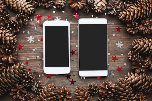 Fondo di legno rustico con due smartphone e decorazioni natalizie.
