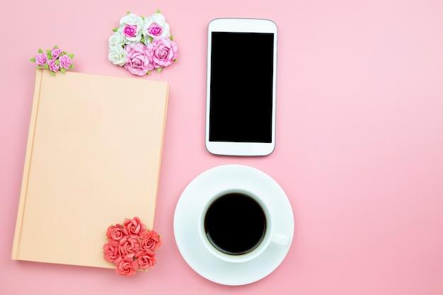 Fondo di rosa della tazza bianca del caffè nero e del telefono cellulare del taccuino