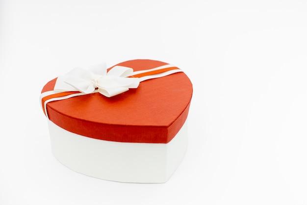 Fondo di san valentino con la scatola vuota di forma del cuore su bianco