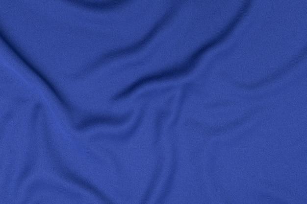 Fondo di struttura del tessuto dell'abbigliamento di sport. vista dall'alto della superficie del tessuto in tessuto. maglia da calcio blu con copyspace.