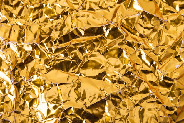 Fondo di struttura della carta della stagnola sgualcito oro.