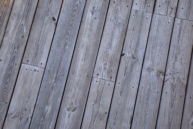 Fondo di un pavimento fatto di traversine di legno grige e vecchie