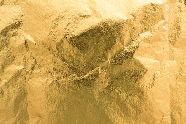 Fondo dorato di struttura della stagnola, elemento brillante della decorazione della carta da imballaggio