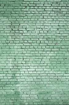 Fondo e struttura quadrati della parete del blocchetto del mattone. dipinto in verde