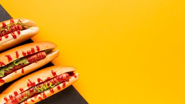 Fondo giallo dello spazio della copia dei hot dog