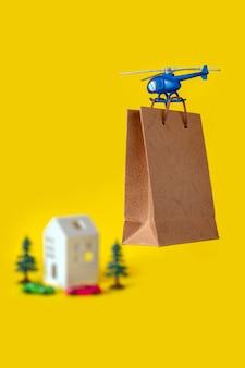Fondo giallo dello spazio della copia della mosca dell'elicottero di consegna dell'albero dell'albero della casa del giocattolo del regalo del sacco di carta