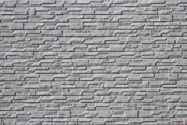 Fondo grigio della parete di progettazione di struttura della superficie delle mattonelle del mattone della massoneria moderna.