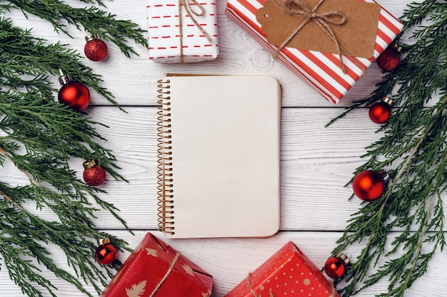 Fondo in legno bianco con rami di conifere e decorazioni natalizie, vista dall'alto