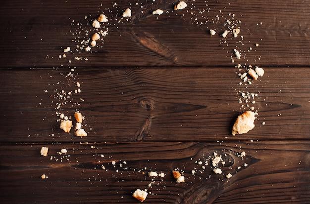 Fondo in legno con briciole di biscotti sotto forma di un cerchio, copia spazio