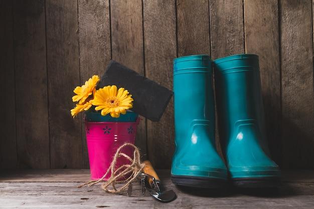 Fondo in legno con stivali e articoli di giardinaggio