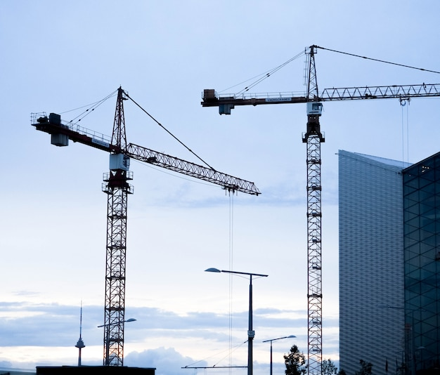 Fondo industriale astratto con le siluette delle gru di costruzione sopra il cielo stupefacente di tramonto