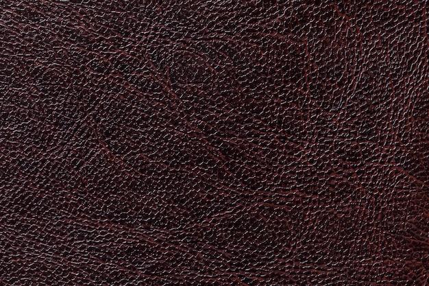 Fondo laccato di struttura del cuoio nero, primo piano, contesto di marrone scuro