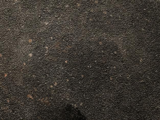 Fondo nero stagionato del muro di cemento