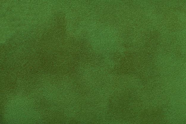 Fondo opaco verde scuro del tessuto della pelle scamosciata, primo piano.