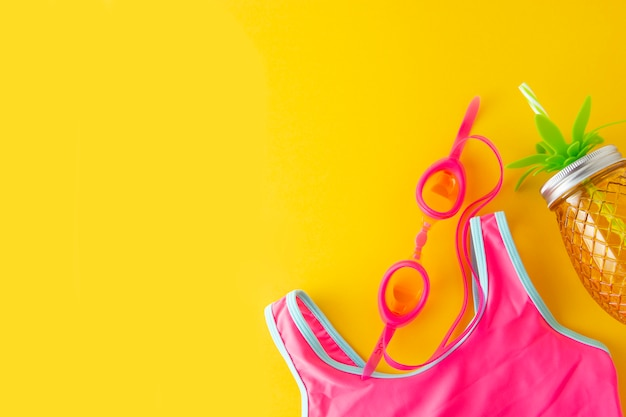 Fondo piatto estate giallo con oggetti da bagno rosa e spiaggia.