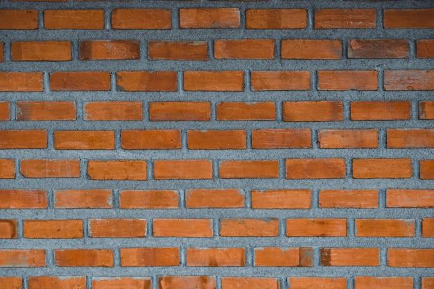 Fondo rosso del frammento del muro di mattoni o costruzione di strato del mattone