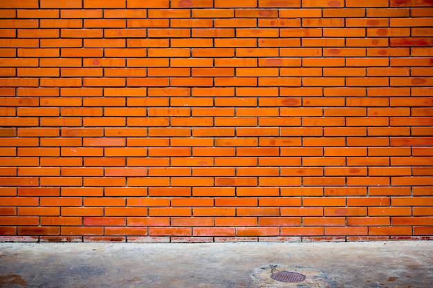 Fondo rosso di struttura del muro di mattoni della via urbana vuota di lerciume