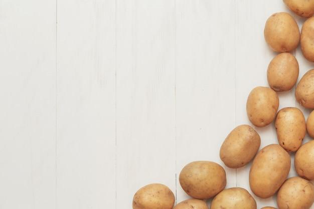 Fondo rustico agricolo - raccolto della patata su una tavola bianca di legno