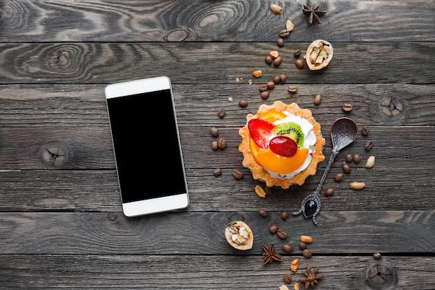 Fondo rustico in legno con crostata di frutta e spezie. smartphone.