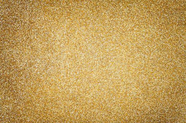 Fondo scintillante dorato dai piccoli lustrini, primo piano. sfondo brillante.