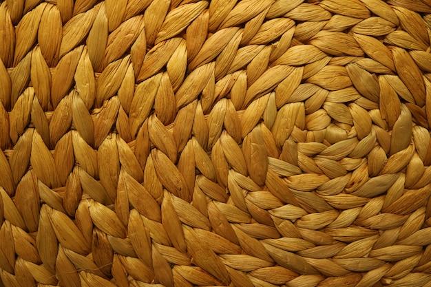 Fondo strutturato di una stuoia di posto del giacinto d'acqua tessuta colore marrone dorato