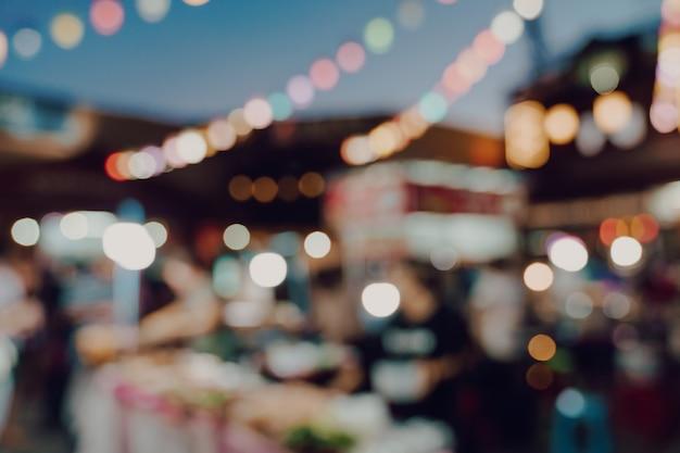 Fondo vago alla gente di festival del mercato di notte che cammina sulla strada.