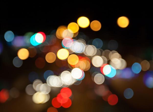 Fondo variopinto del bokeh delle iluminazioni pubbliche della città di notte, concetto di oscurità