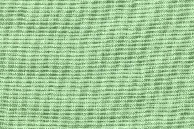 Fondo verde chiaro da una materia tessile con il modello di vimini, primo piano.