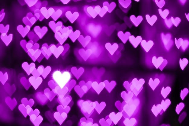 Fondo viola porpora rosa dell'estratto del bokeh del cuore