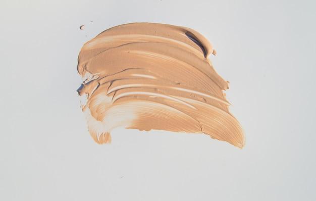Fondotinta beige per il trucco, tocchi cosmetici su sfondo bianco