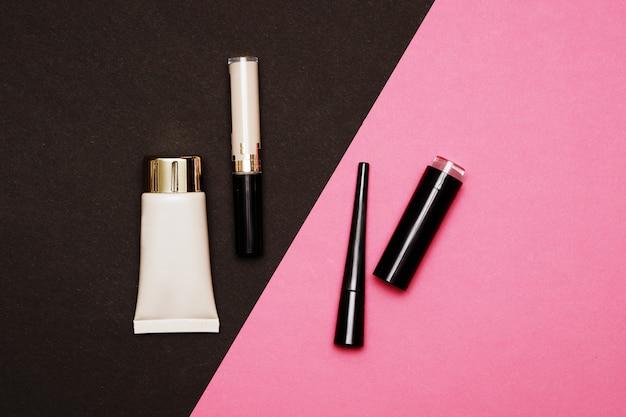Fondotinta, correttore, eyeliner e rossetto su uno sfondo nero e rosa. struttura