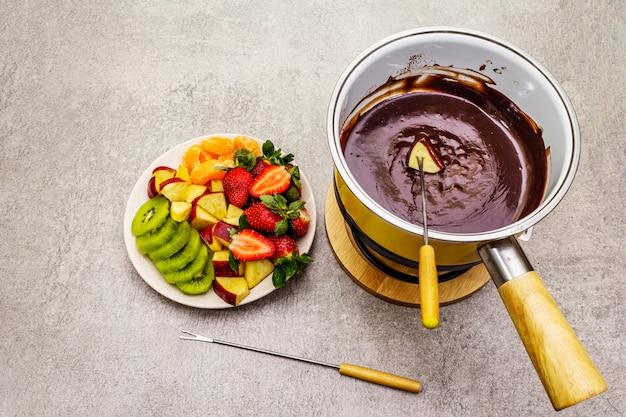 Fonduta di cioccolato. frutta fresca assortita, due tipi di cioccolato. ingredienti per cucinare un dolce dolce romantico.