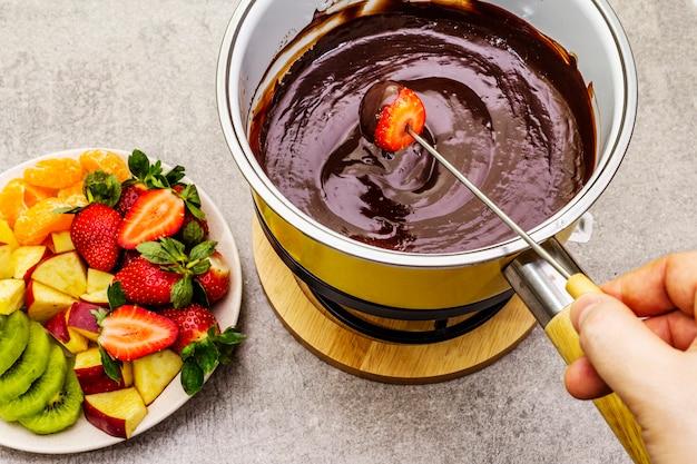 Fonduta di cioccolato. frutta fresca assortita, due tipi di cioccolato, mano maschile. ingredienti per cucinare un dolce dolce romantico.