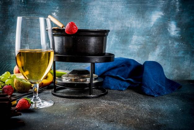 Fonduta di cioccolato nella tradizionale pentola per fonduta, con forchette, vino bianco, vari frutti di bosco e frutta assortiti, spazio di copia