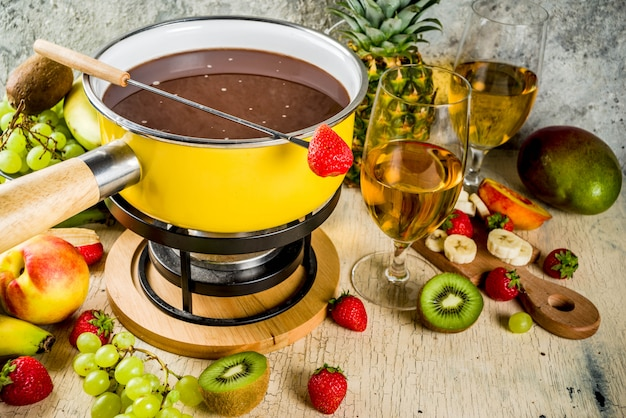 Fonduta di cioccolato nella tradizionale pentola per fonduta, con forchette, vino bianco, vari frutti di bosco e frutta assortiti