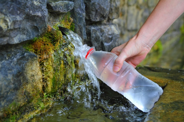 Fonte della mano di riempimento della bottiglia di acqua sorgiva