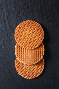 Food concept stroopwafel, sciroppo di caramello croccante waffle olandesi su pietra nera ardesia