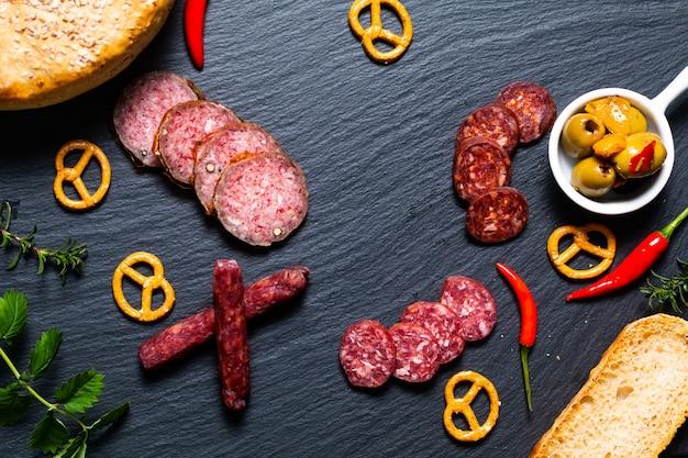Food party con diversi tipi di carne e pane fatto in casa su pietra ardesia nera
