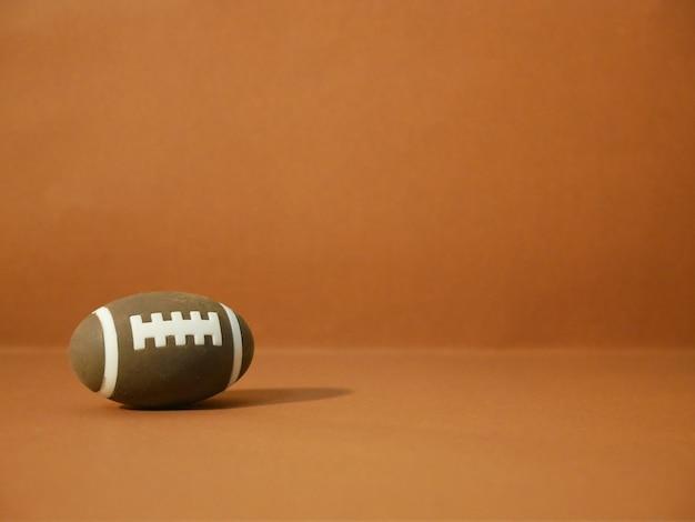 Football americano con lo spazio della copia su fondo marrone.