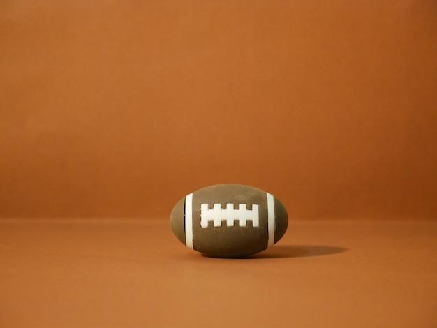 Football americano con lo spazio della copia su fondo marrone