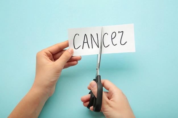 Forbici che tagliano un pezzo di carta con la parola cancro. simbolo di consapevolezza del cancro al seno. lotta contro il cancro concetto.