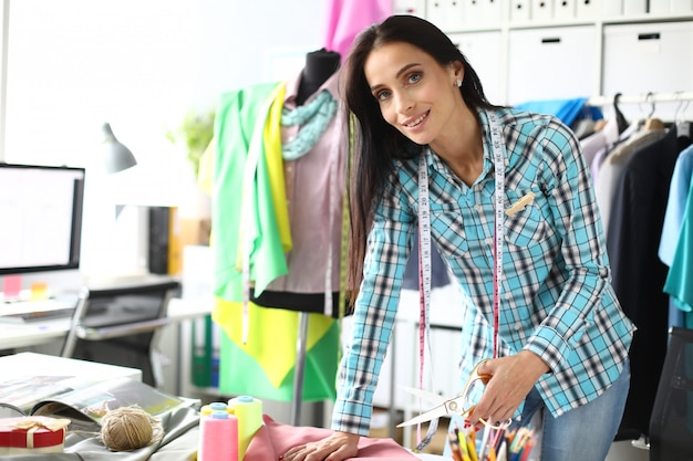 Forbici cucitrice donna taglia tessuto in negozio di cucito e riparazioni. concetto di sviluppo di piccole e medie imprese.