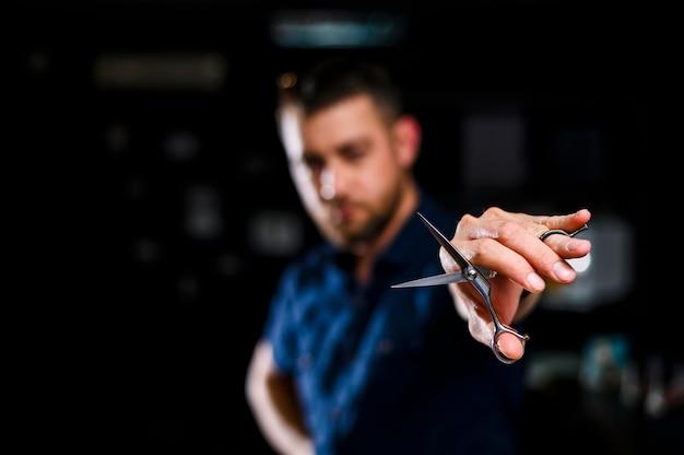 Forbici della tenuta del barbiere del primo piano