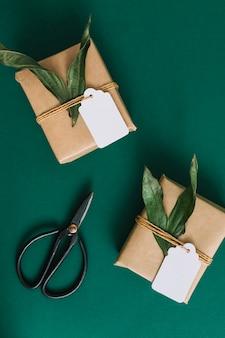 Forbici e due scatole regalo su sfondo verde