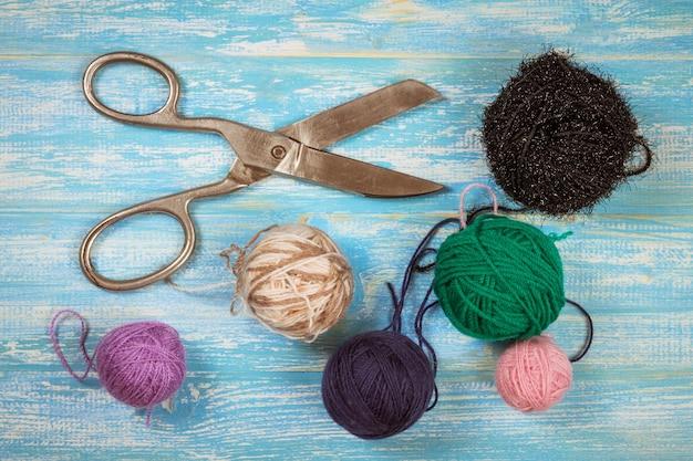 Forbici e palle di lana d'annata su una tavola di legno blu.