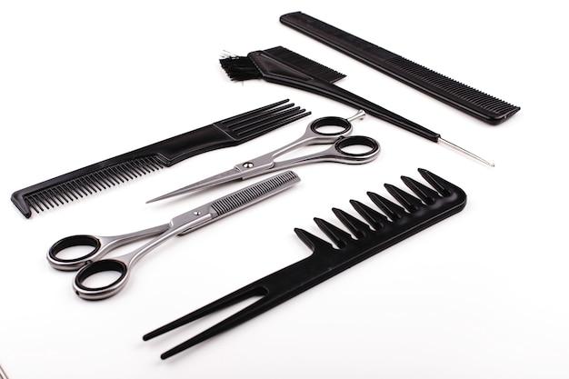 Forbici e pettini per il taglio dei capelli e il trattamento si trovano su un tavolo bianco