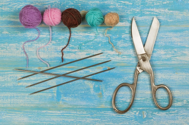 Forbici, ferri da maglia e fili colorati su un tavolo di legno blu.