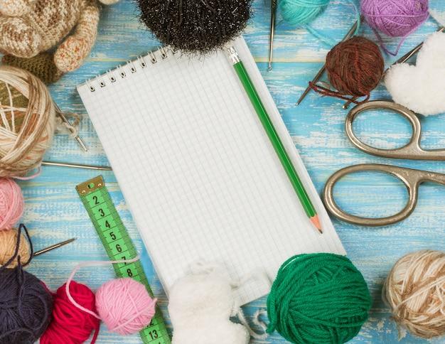 Forbici, gomitoli di lana, nastro e taccuino di misurazione su una tavola di legno.