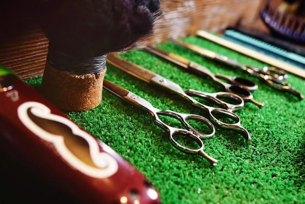 Forbici per il taglio su una stuoia verde nel negozio di barbiere