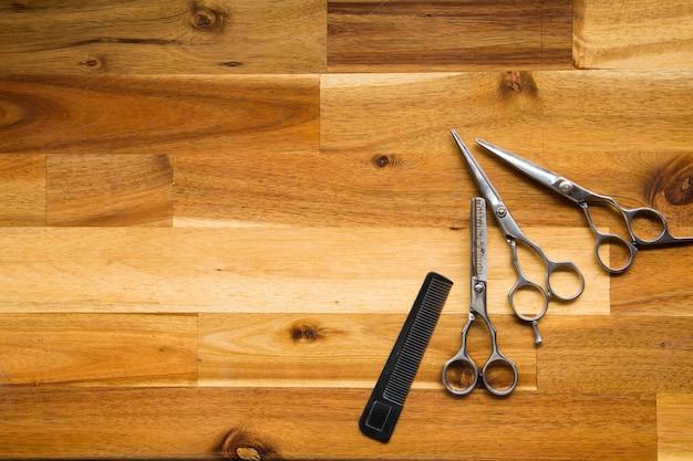 Forbici professionali alla moda del barbiere su fondo di legno, taglio dei capelli e forbice d'assottigliamento